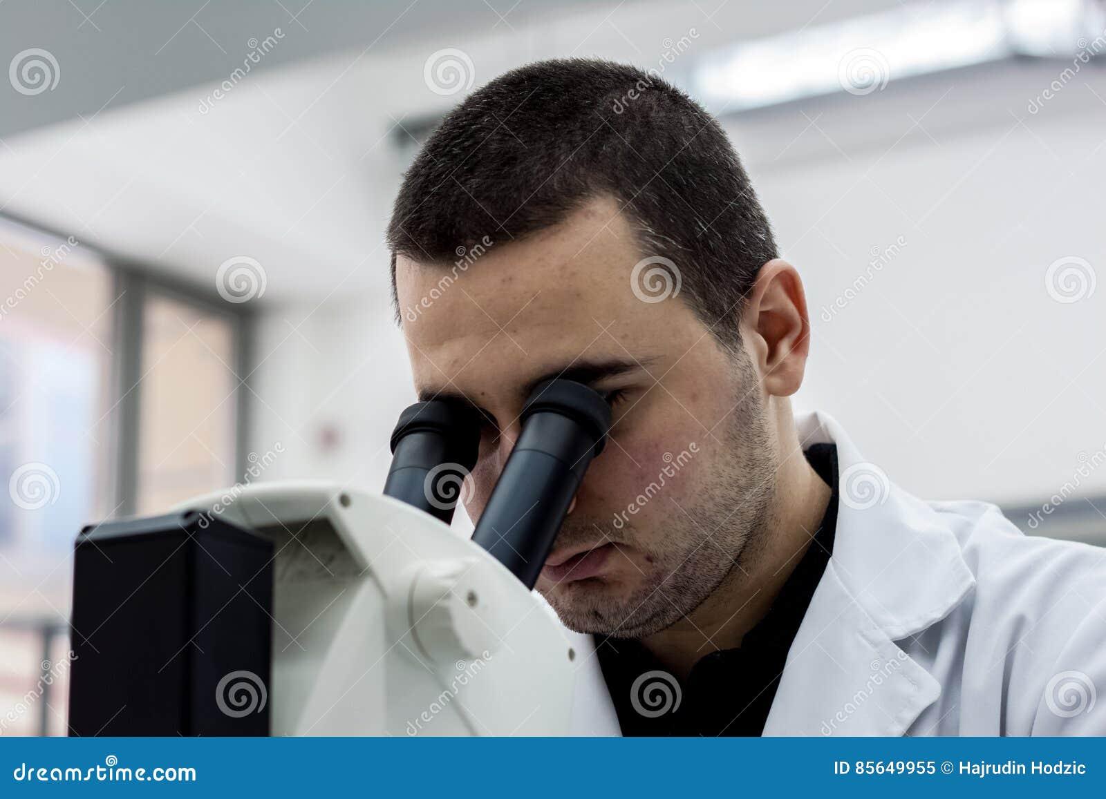 Docteur médical ou scientifique féminin d homme de chercheur regardant le throu