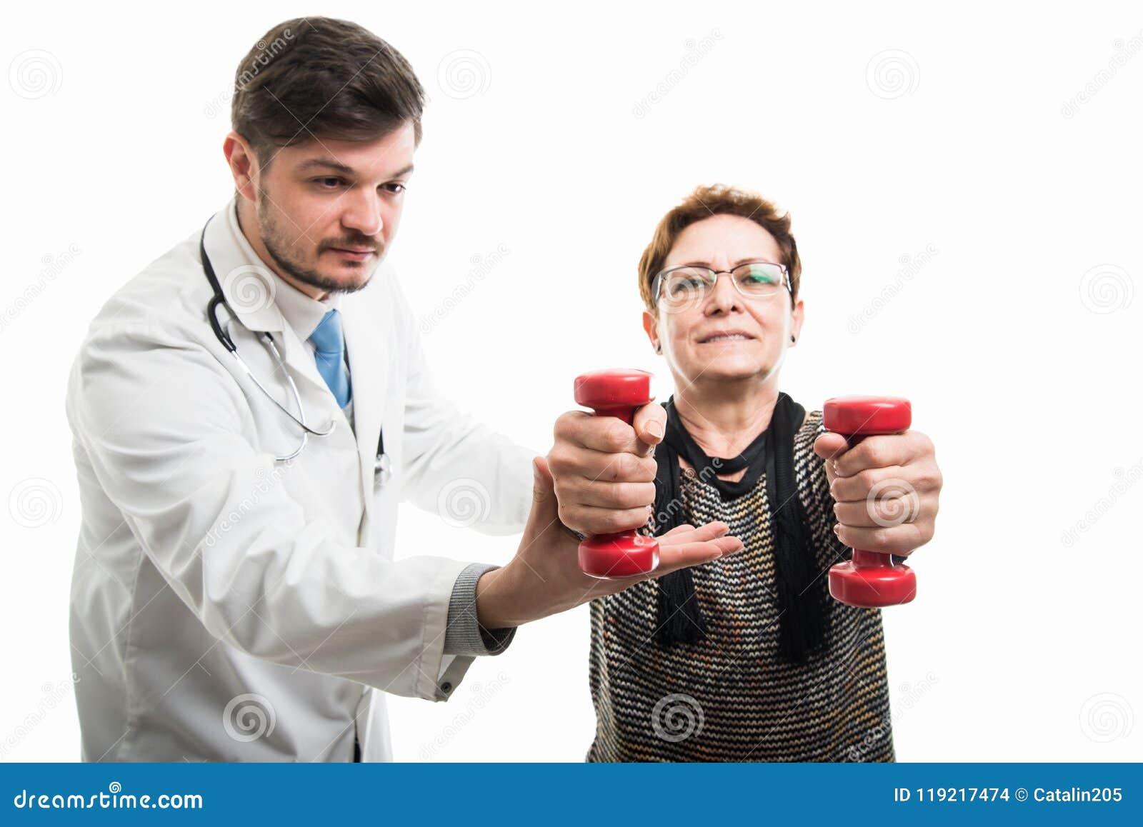 Docteur masculin aidant le patient féminin travaillant avec l haltère