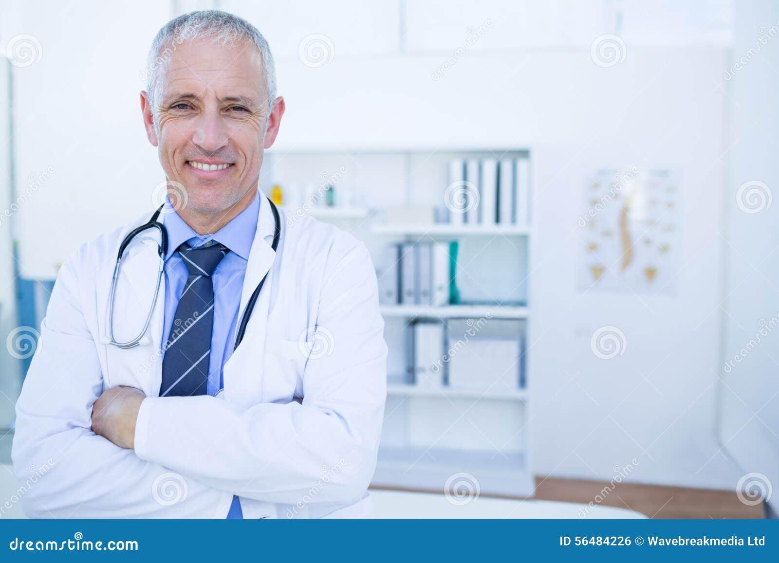 Docteur masculin heureux regardant l appareil-photo avec des bras croisés