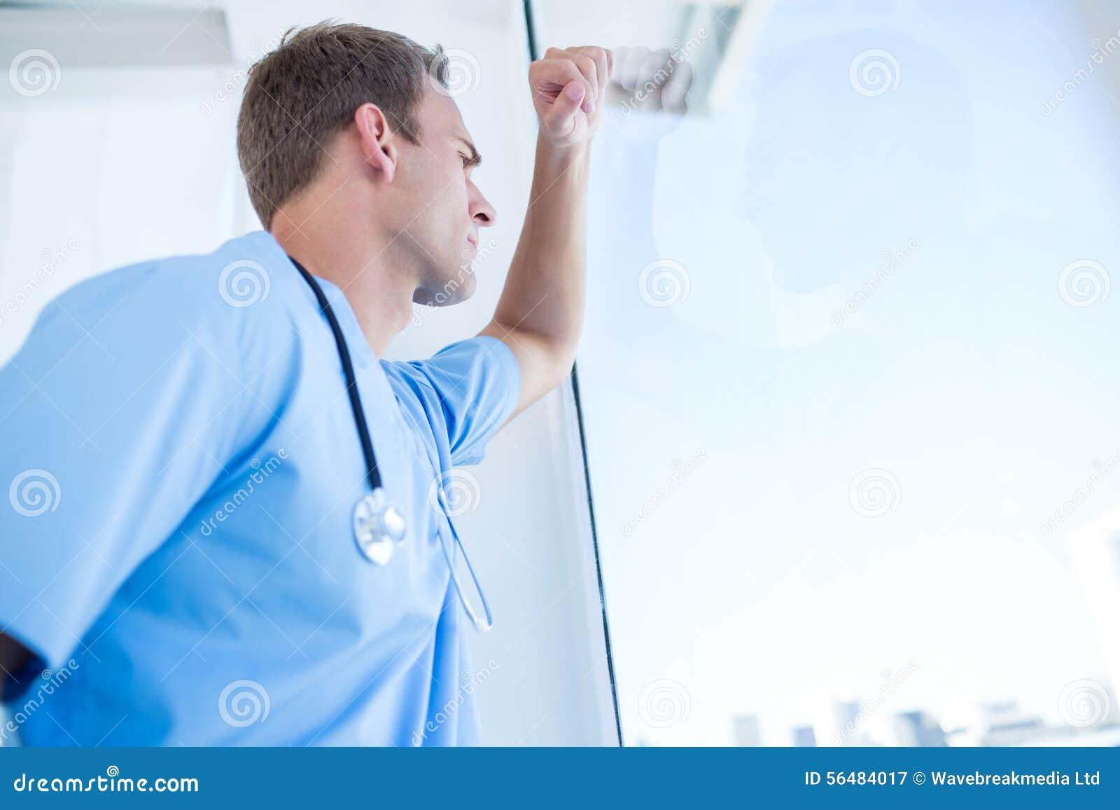 Docteur réfléchi regardant par les fenêtres
