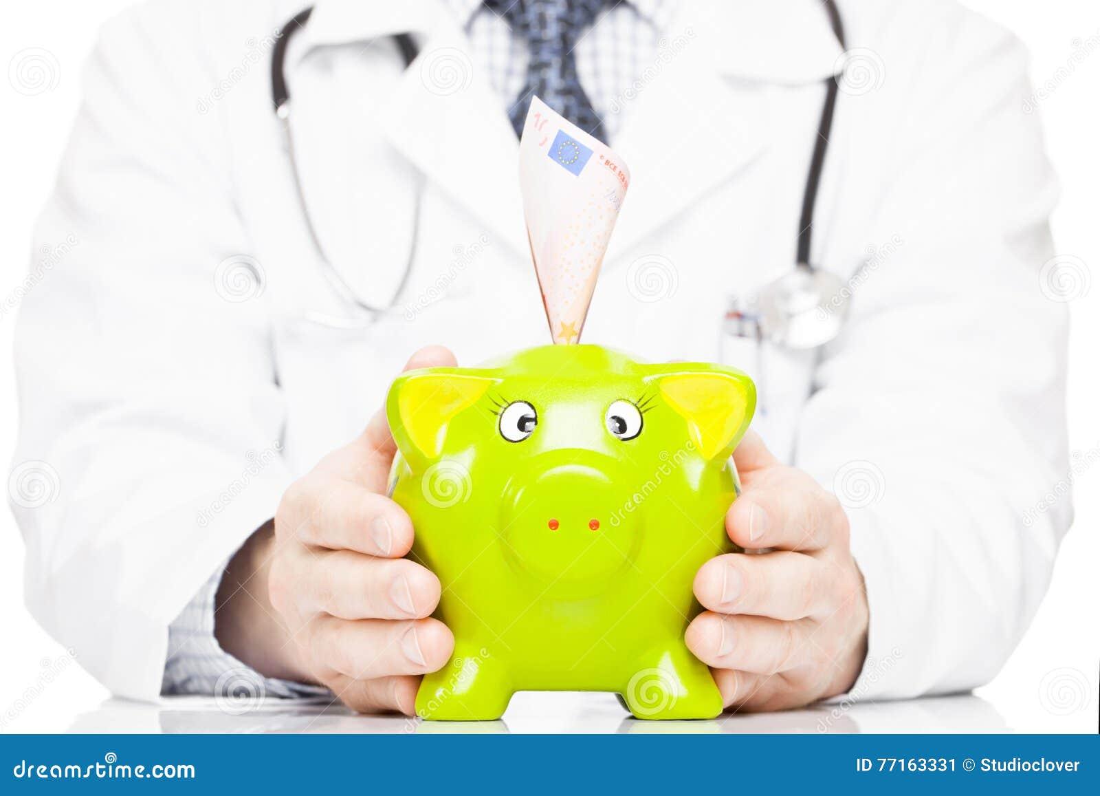 Docteur tenant la tirelire comme idée de l épargne pour des dépenses médicales