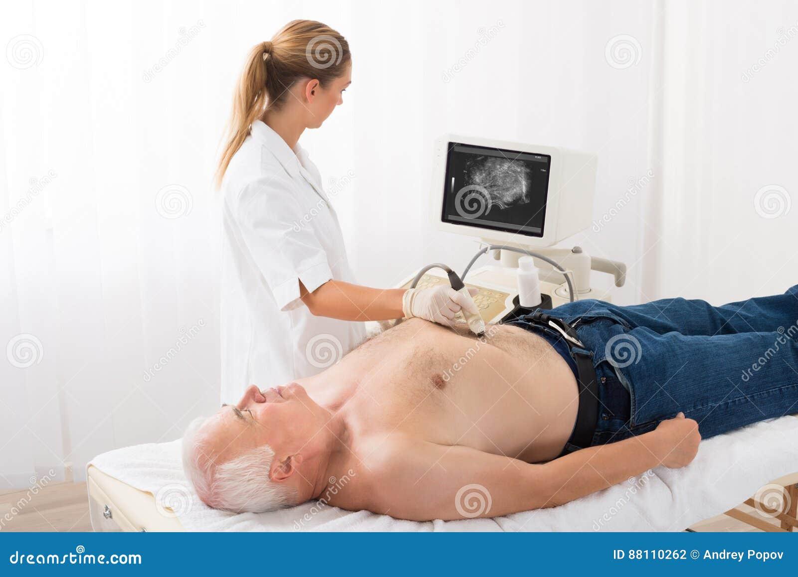 Docteur Using Ultrasound Scan sur l abdomen du patient masculin