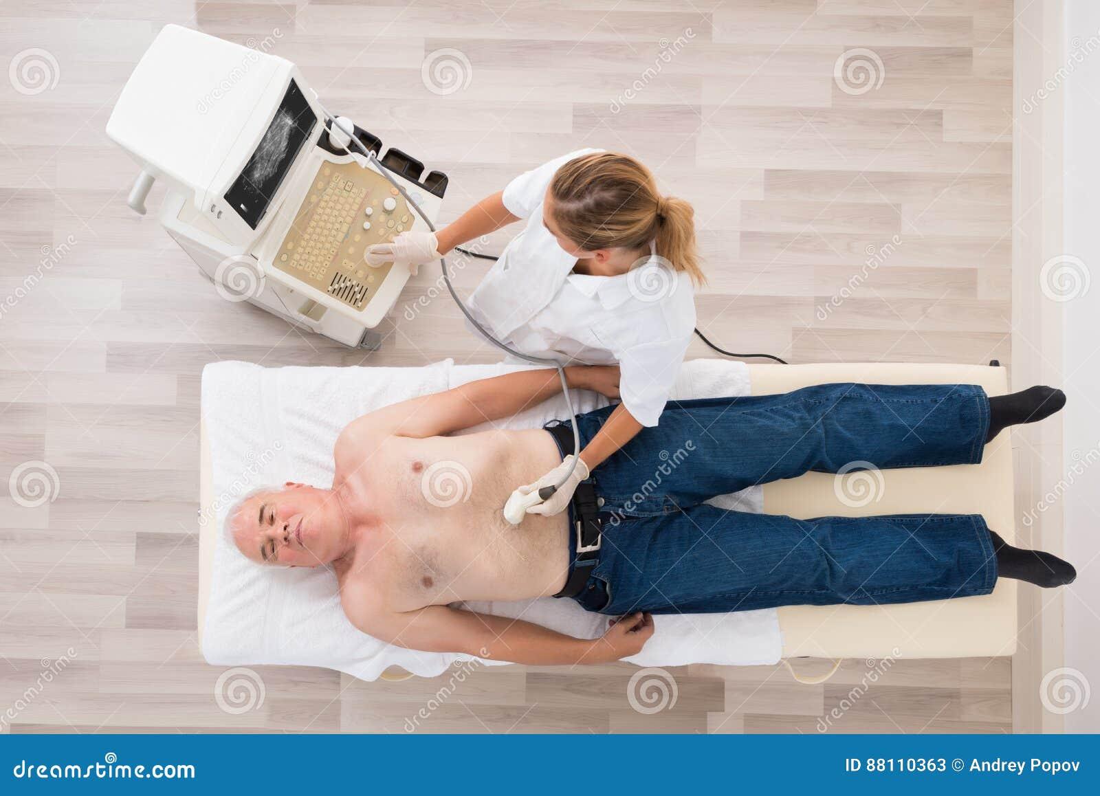Docteur Using Ultrasound Scan sur l abdomen du patient masculin supérieur
