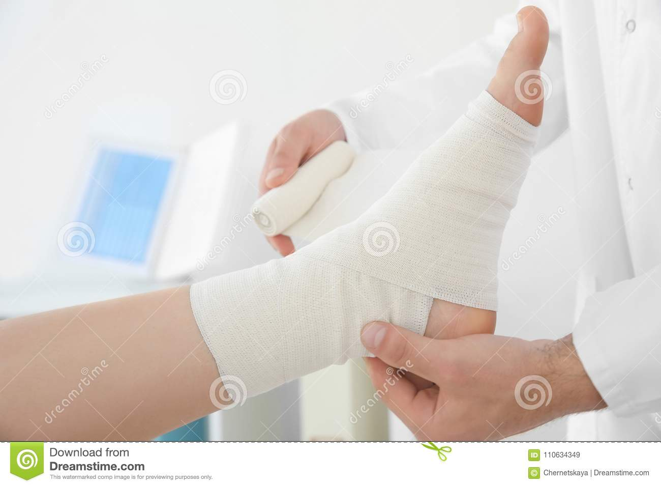 Doctor applying bandage onto patient`s leg in clinic,