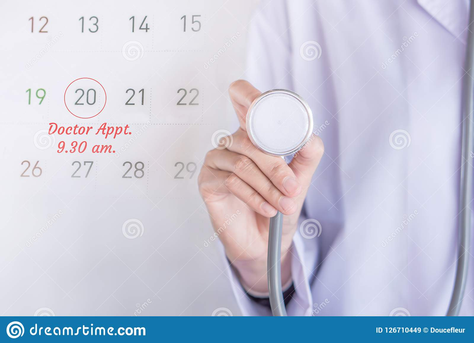 Doctor appointment concept background with note on calendar and doctor hand holding stethoscope