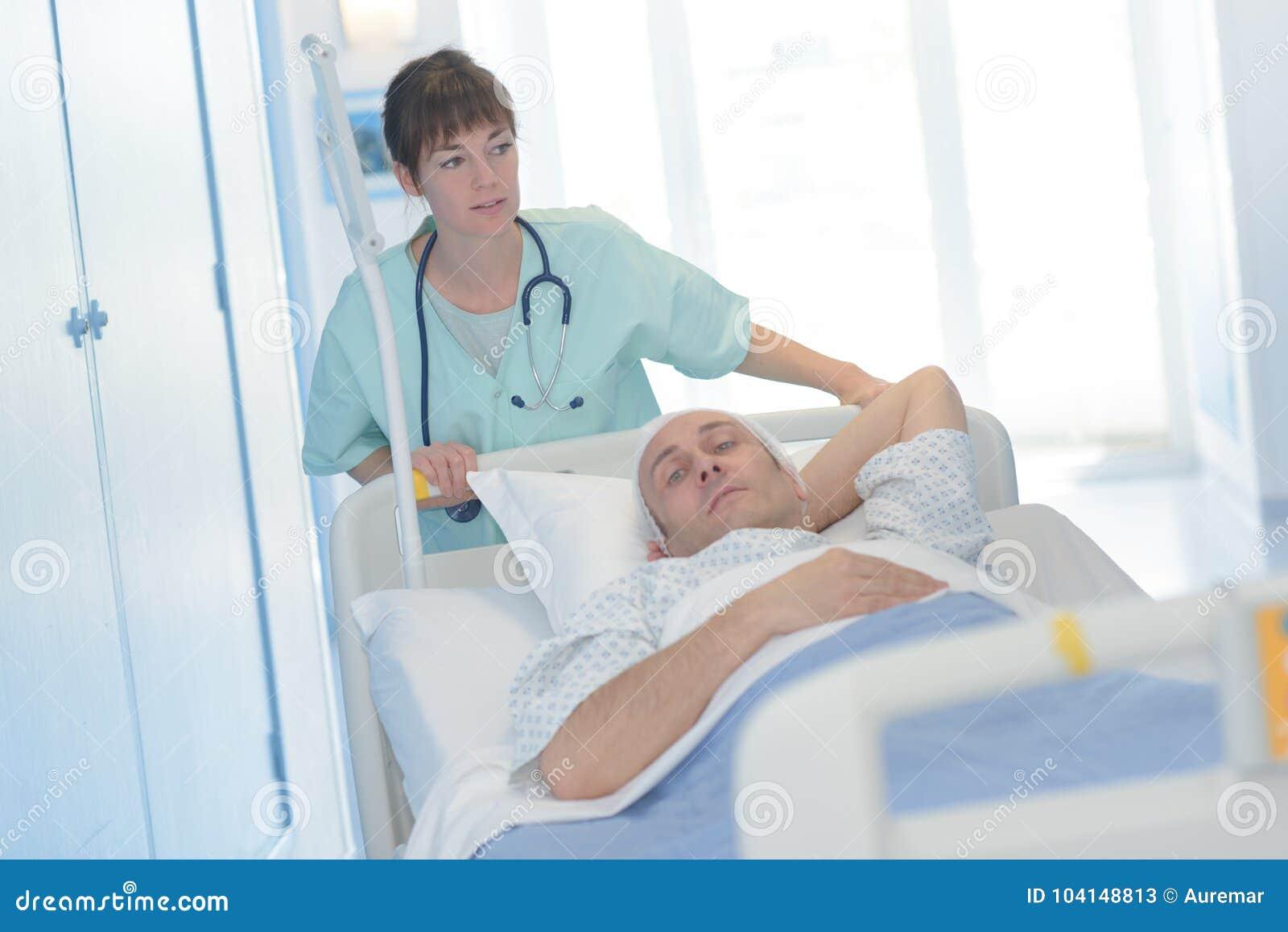 Doctor bonito que transporta al paciente que pone en ensanchador