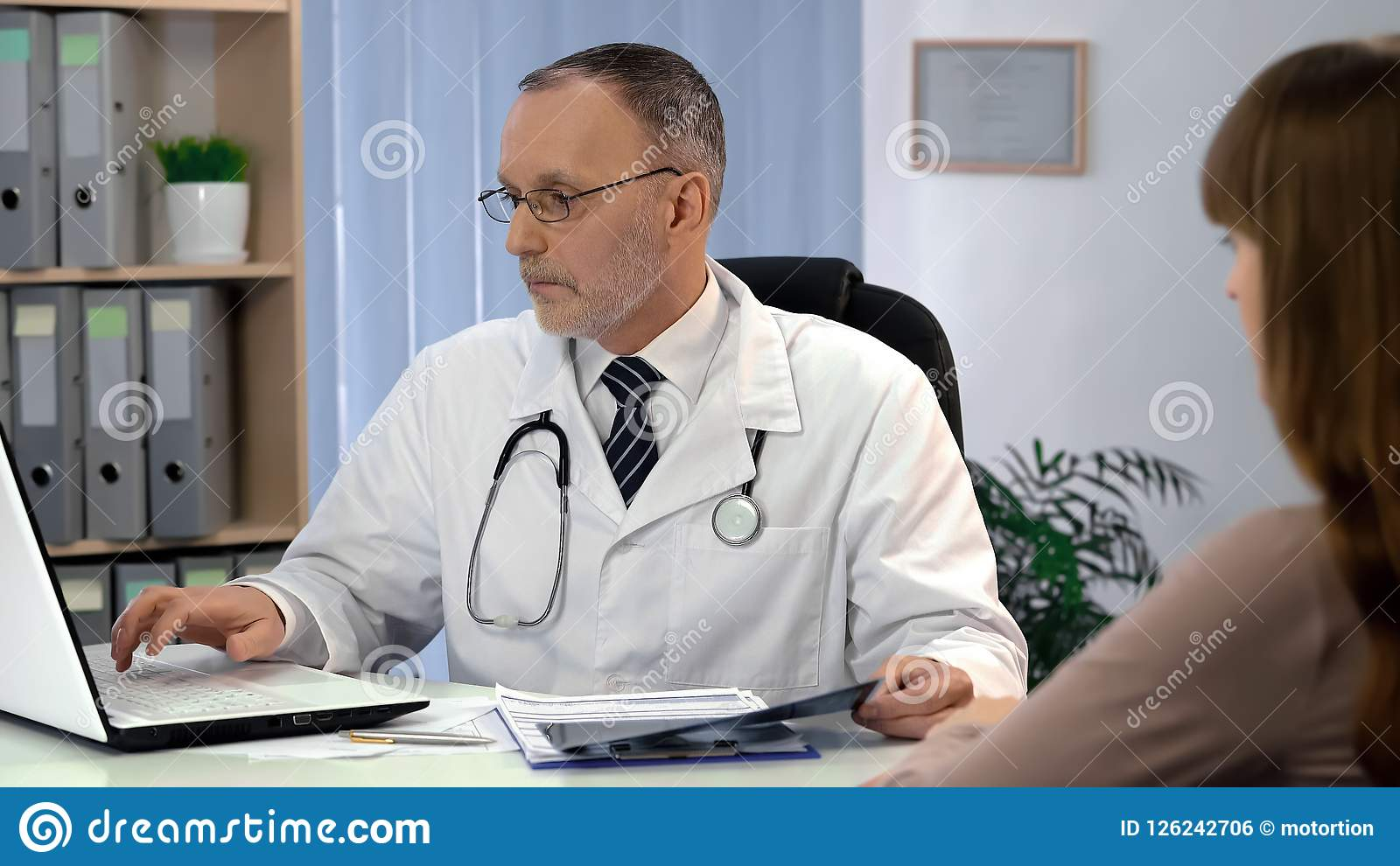 Doctor checking analysis on laptop, holding x-ray, digital devices replace paper