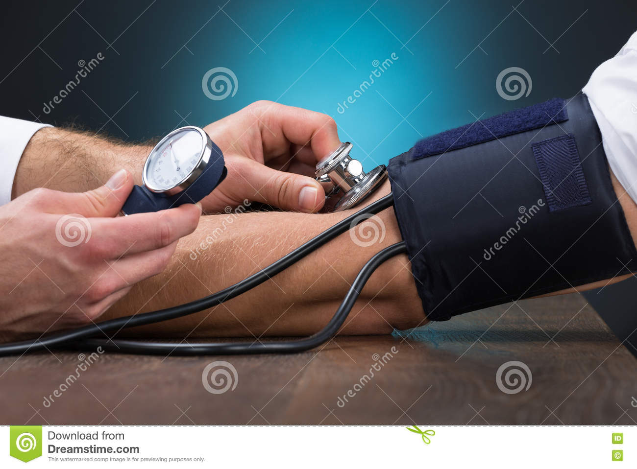 Doctor Checking Blood Pressure Of Patient At Table