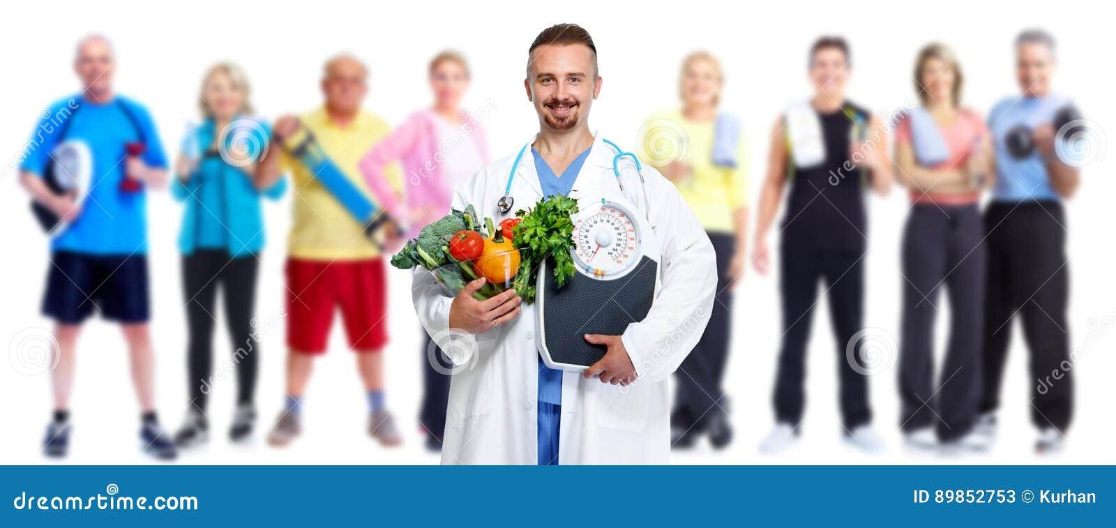 Doctor con las verduras y el grupo de gente de la aptitud