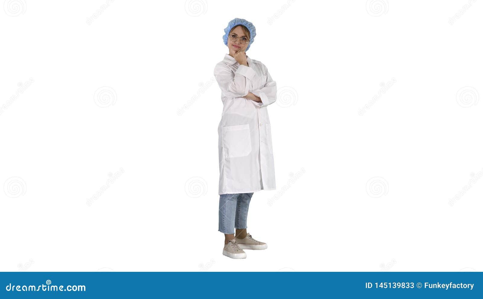 Doctor confiado sonriente de la mujer joven que se coloca con los brazos cruzados encima en el fondo blanco