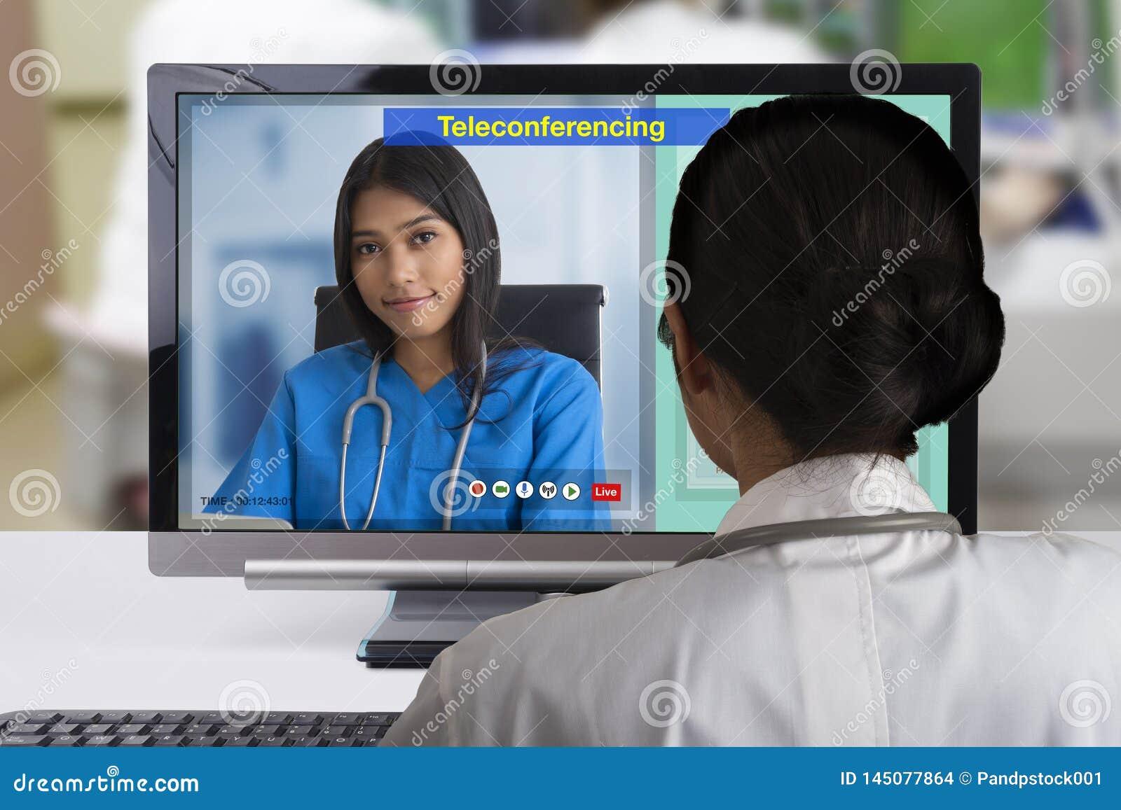 Doctor de dos hembras usando tecnología de la teleconferencia al discutsion sobre caso paciente