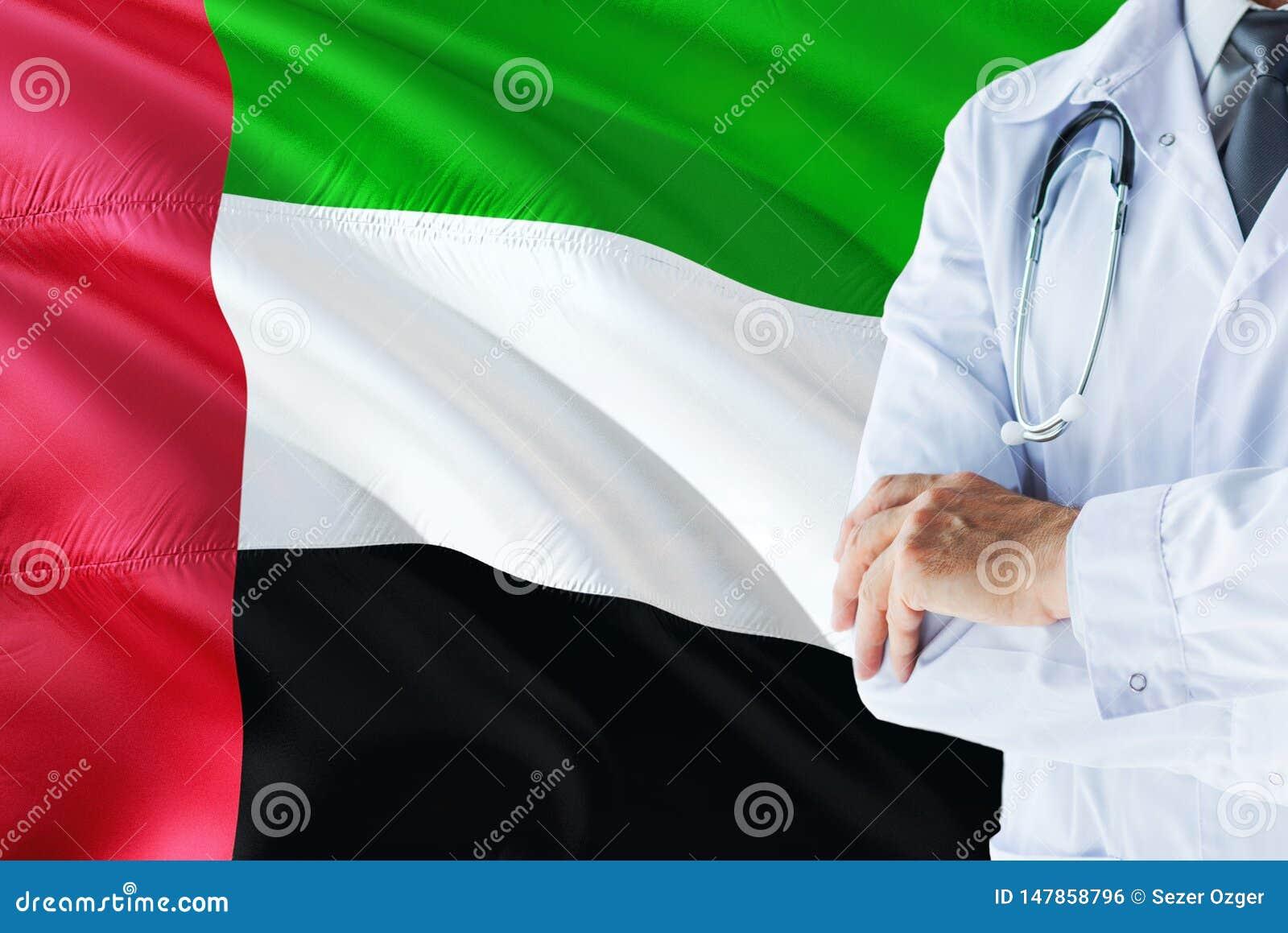 Doctor de Emirian que se coloca con el estetoscopio en fondo de la bandera de United Arab Emirates Concepto de sistema sanitario