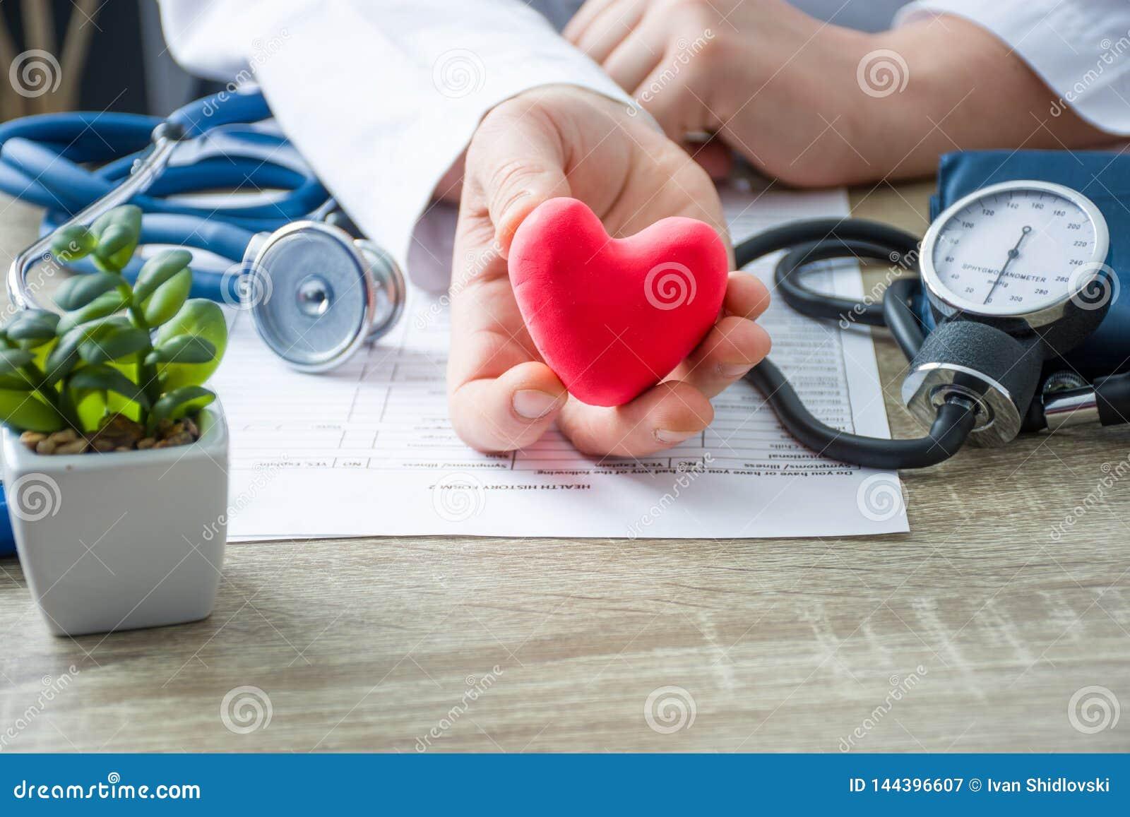 Doctor de la medicina interna y cardiólogo que se sostiene en sus manos y demostraciones a la figura paciente del corazón de la t