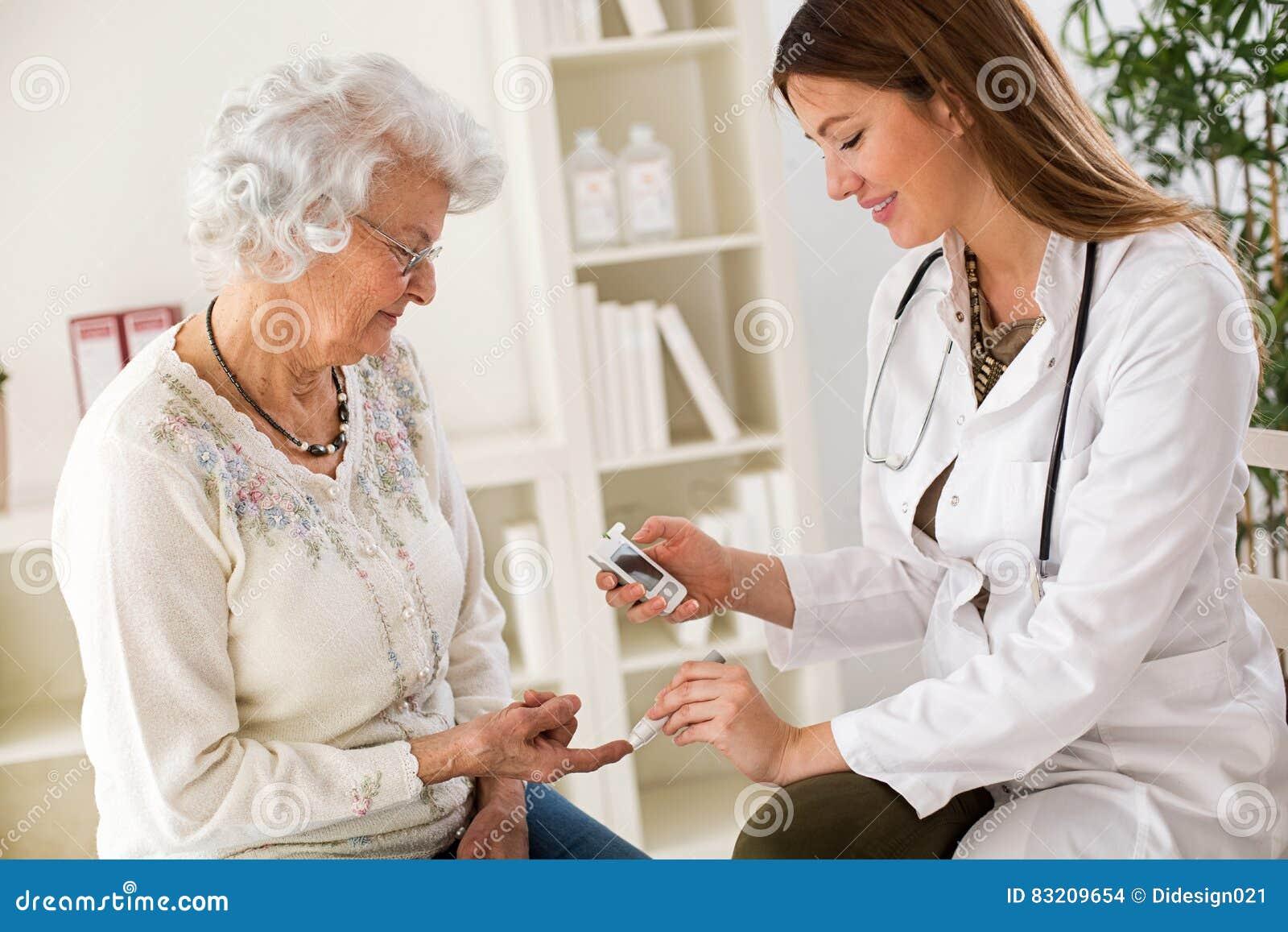 Doctor de sexo femenino joven que hace el análisis de sangre de la diabetes en mujer mayor