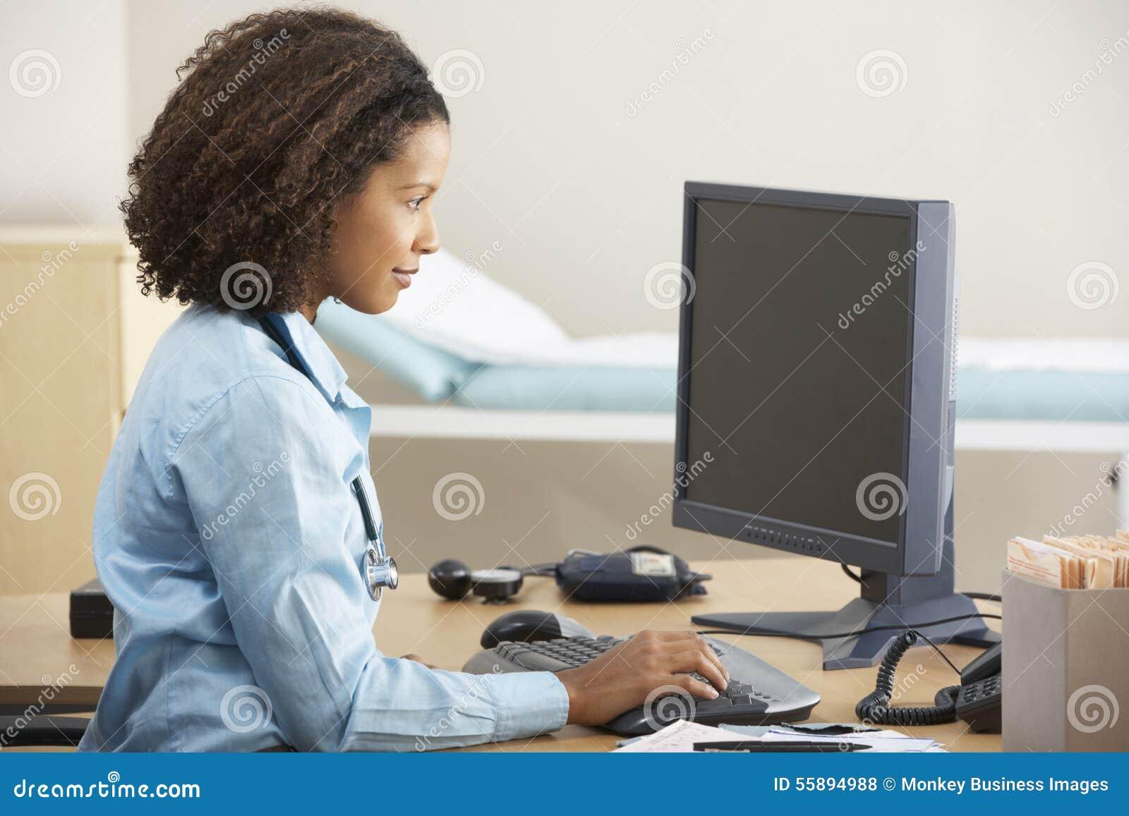 Doctor de sexo femenino joven que trabaja en el ordenador en el escritorio