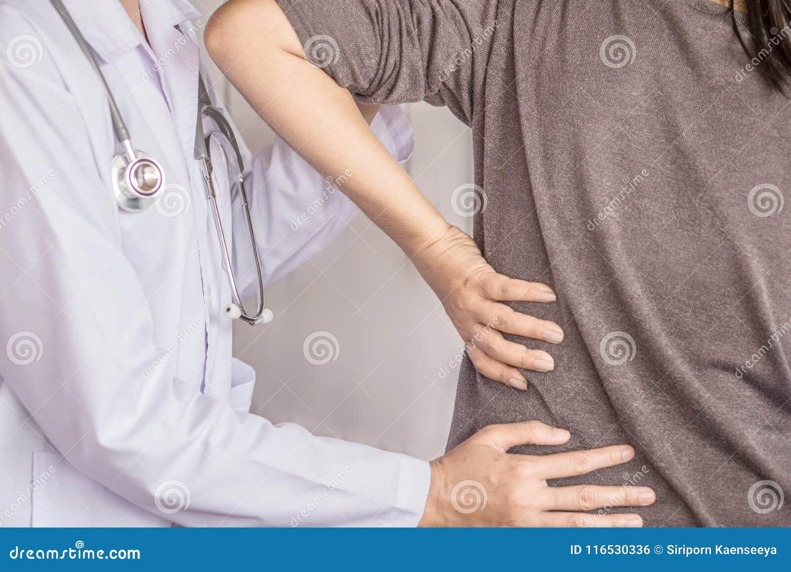 Doctor de sexo femenino que examina un sufrimiento paciente del dolor de espalda
