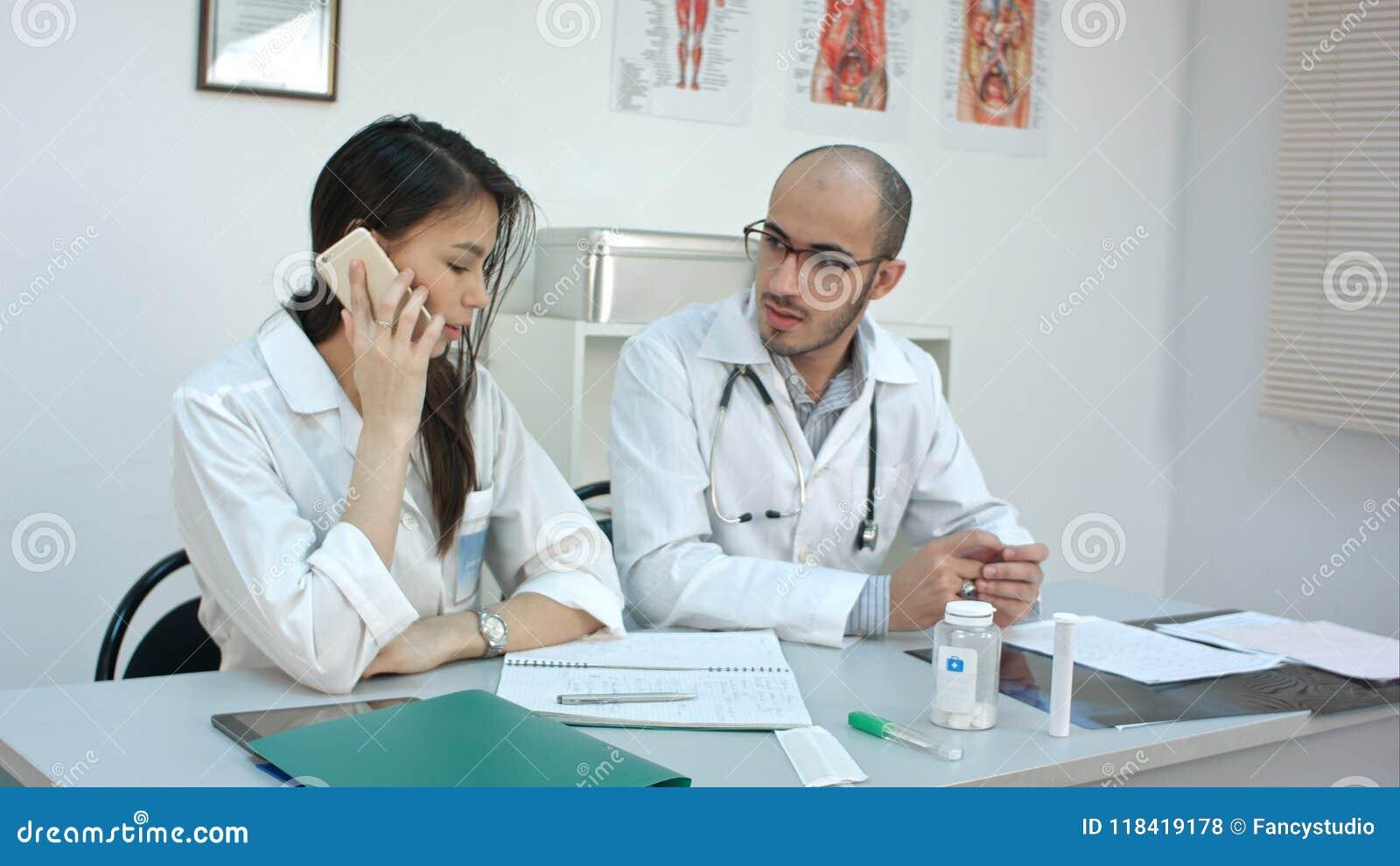 Doctor de sexo femenino que habla en el teléfono que pide a su compañero de trabajo masculino consejo