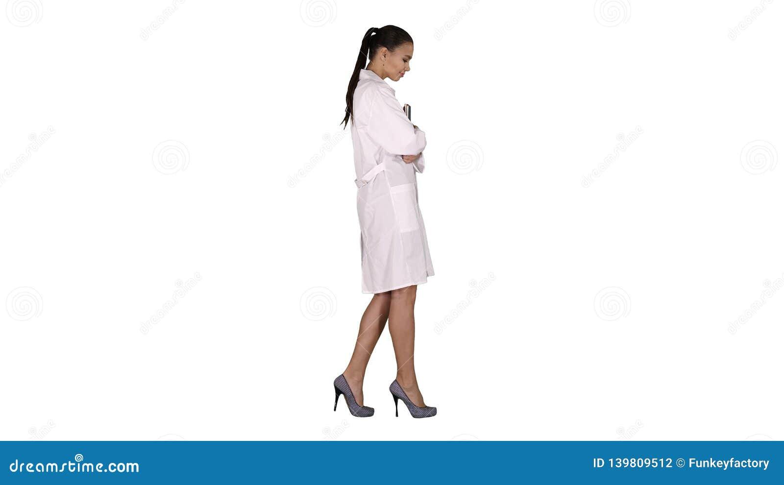 Doctor de sexo femenino sonriente feliz que camina llevando a cabo los cuadernos o los documentos en el fondo blanco