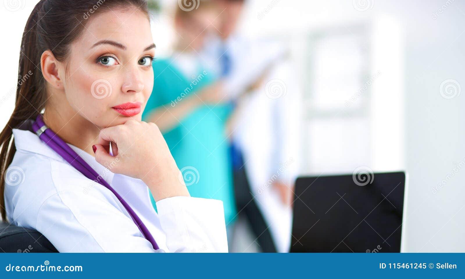 Doctor de sexo femenino sonriente de los jóvenes hermosos que se sienta en el escritorio