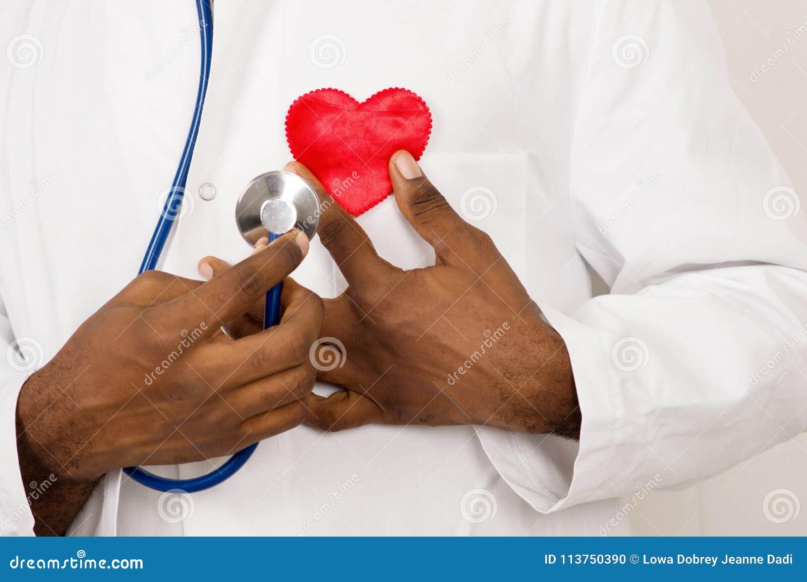 Doctor de sexo masculino con el estetoscopio que lleva a cabo el corazón