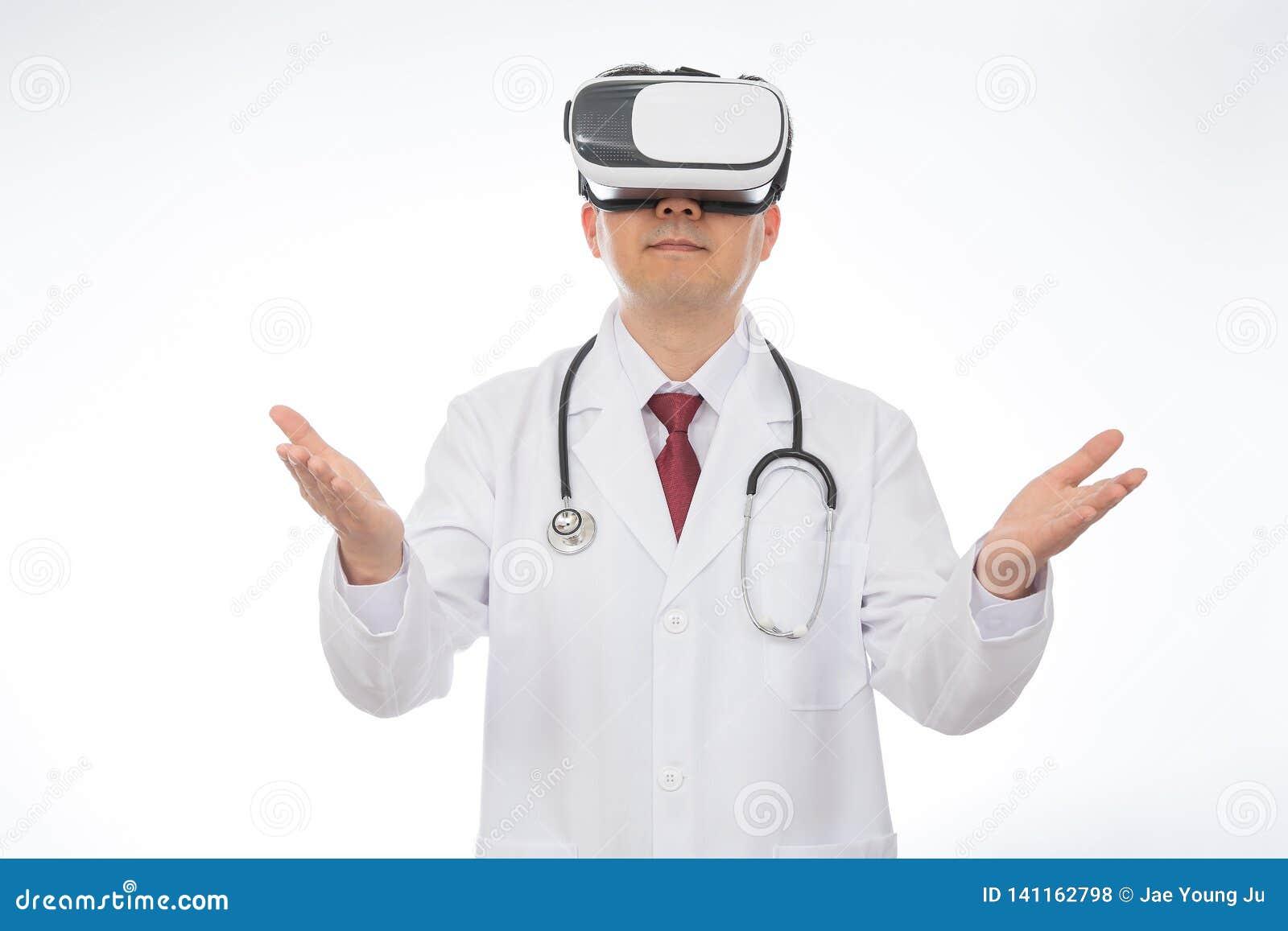 Doctor de sexo masculino que lleva los vidrios de la realidad virtual aislados en el fondo blanco