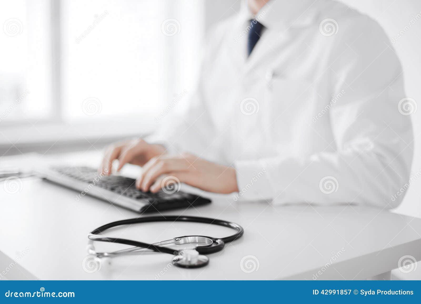 Doctor de sexo masculino que mecanografía en el teclado