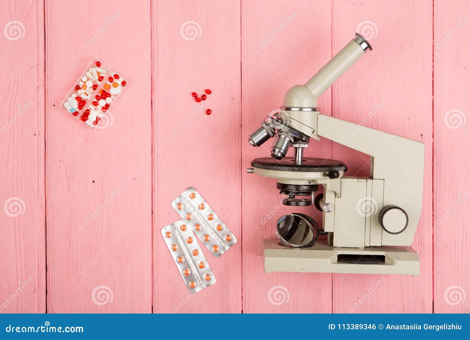 Doctor del científico del lugar de trabajo - microscopio, píldoras en la tabla de madera rosada
