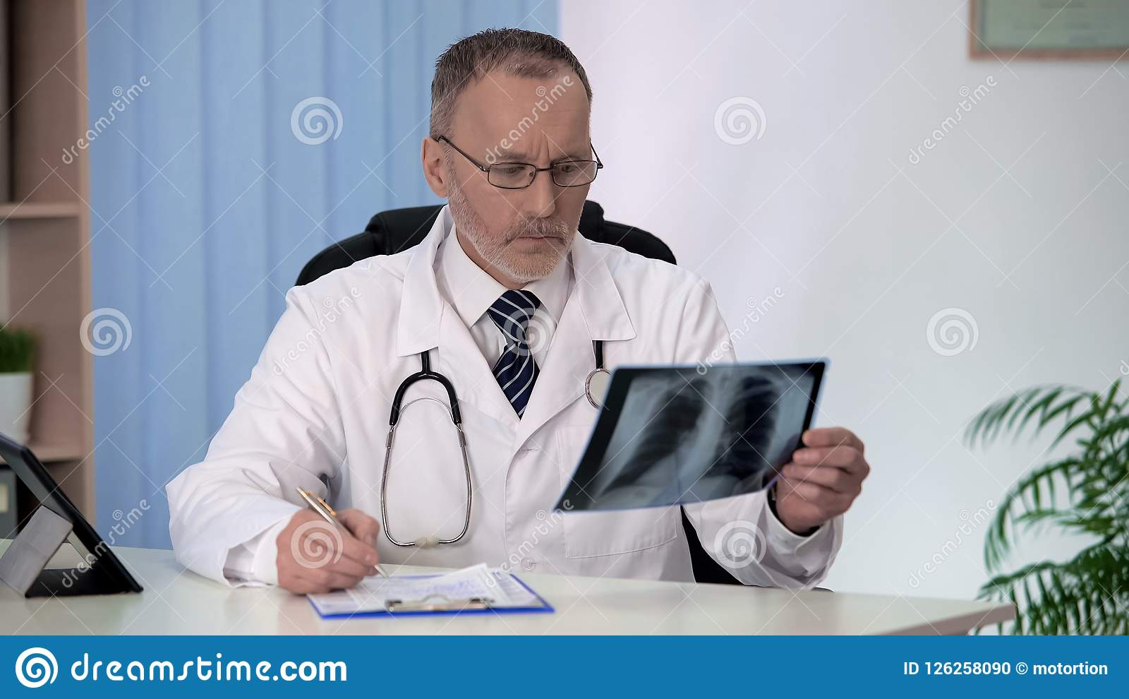 Doctor examining chest lung x-ray, filling patients medical form, flu epidemic