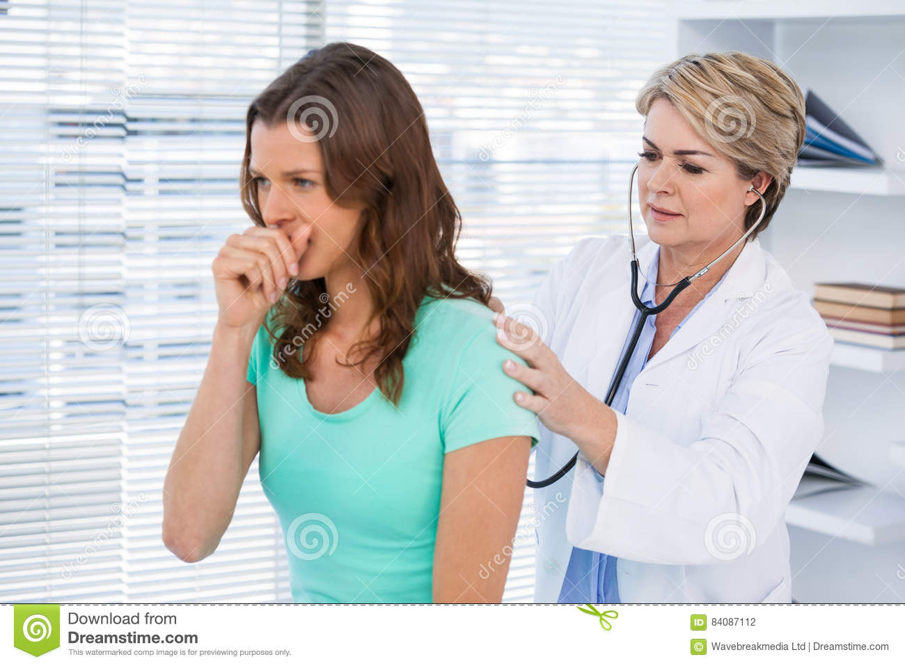 Doctor examining coughing patient with stethoscope