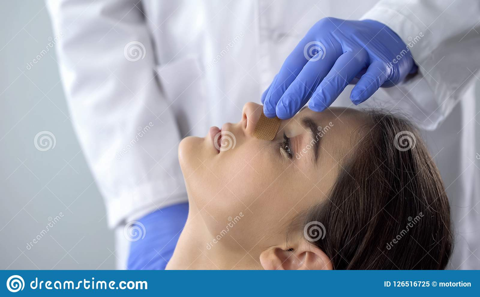 Doctor examining patient nose after rhinoplasty surgery, medical aid, healthcare