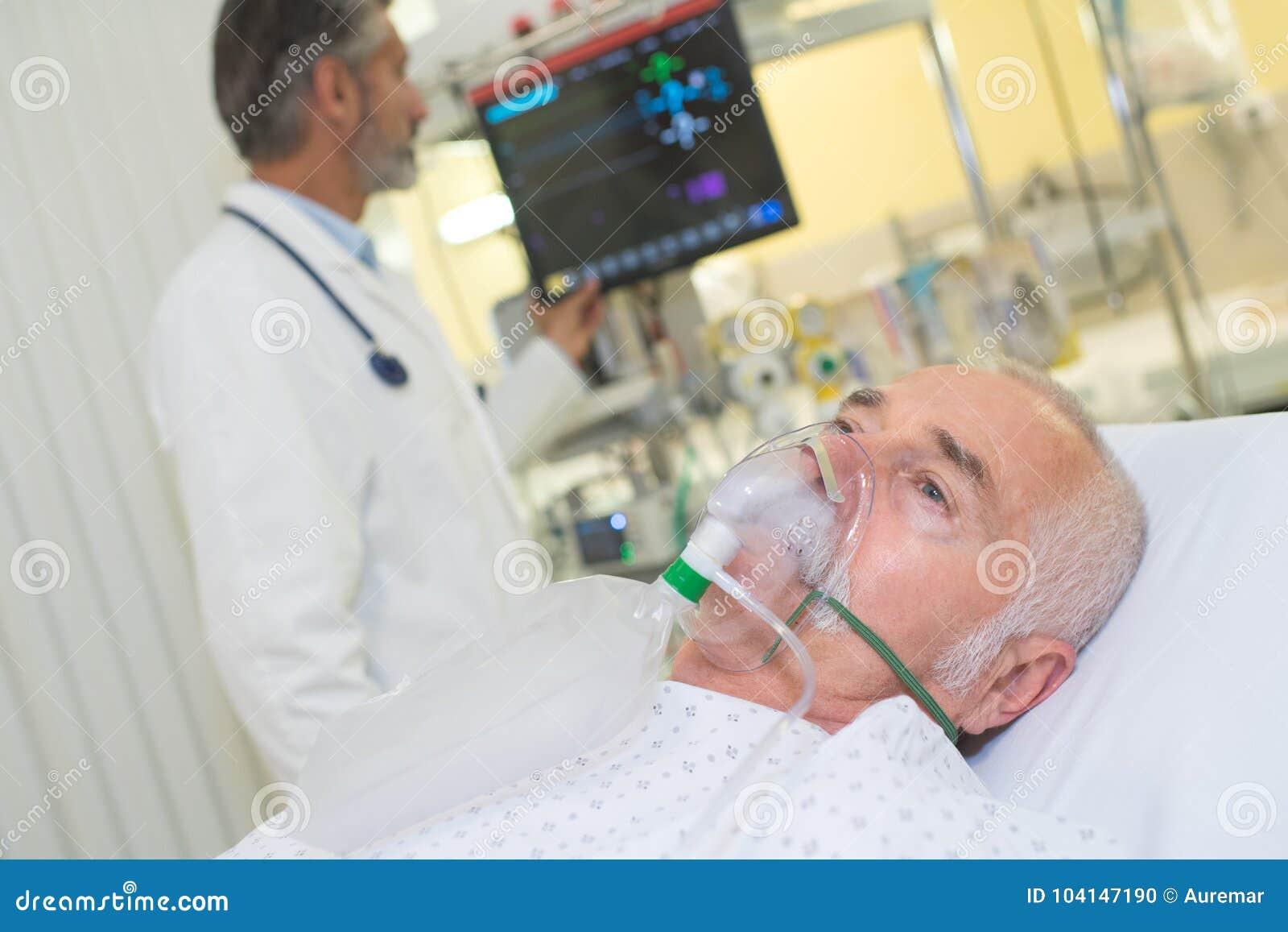 Doctor examining patient wearing oxygen mask