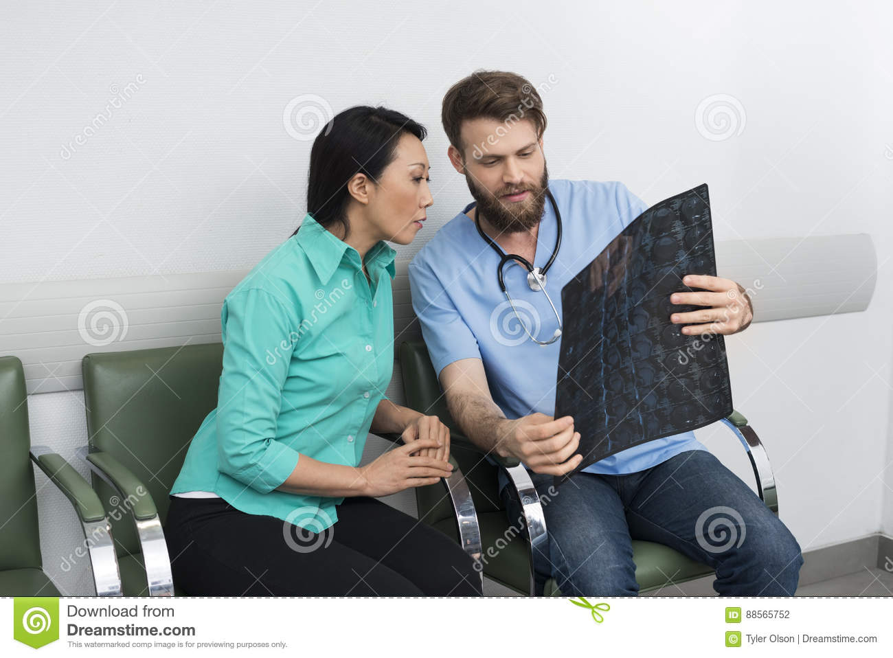 Doctor Explaining X-ray To Patient At Hospital Lobby