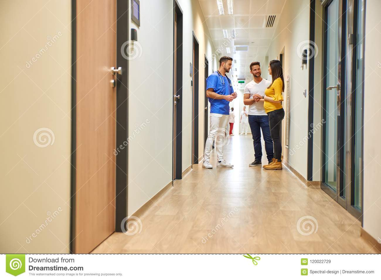 A doctor and the future parents on the hallway