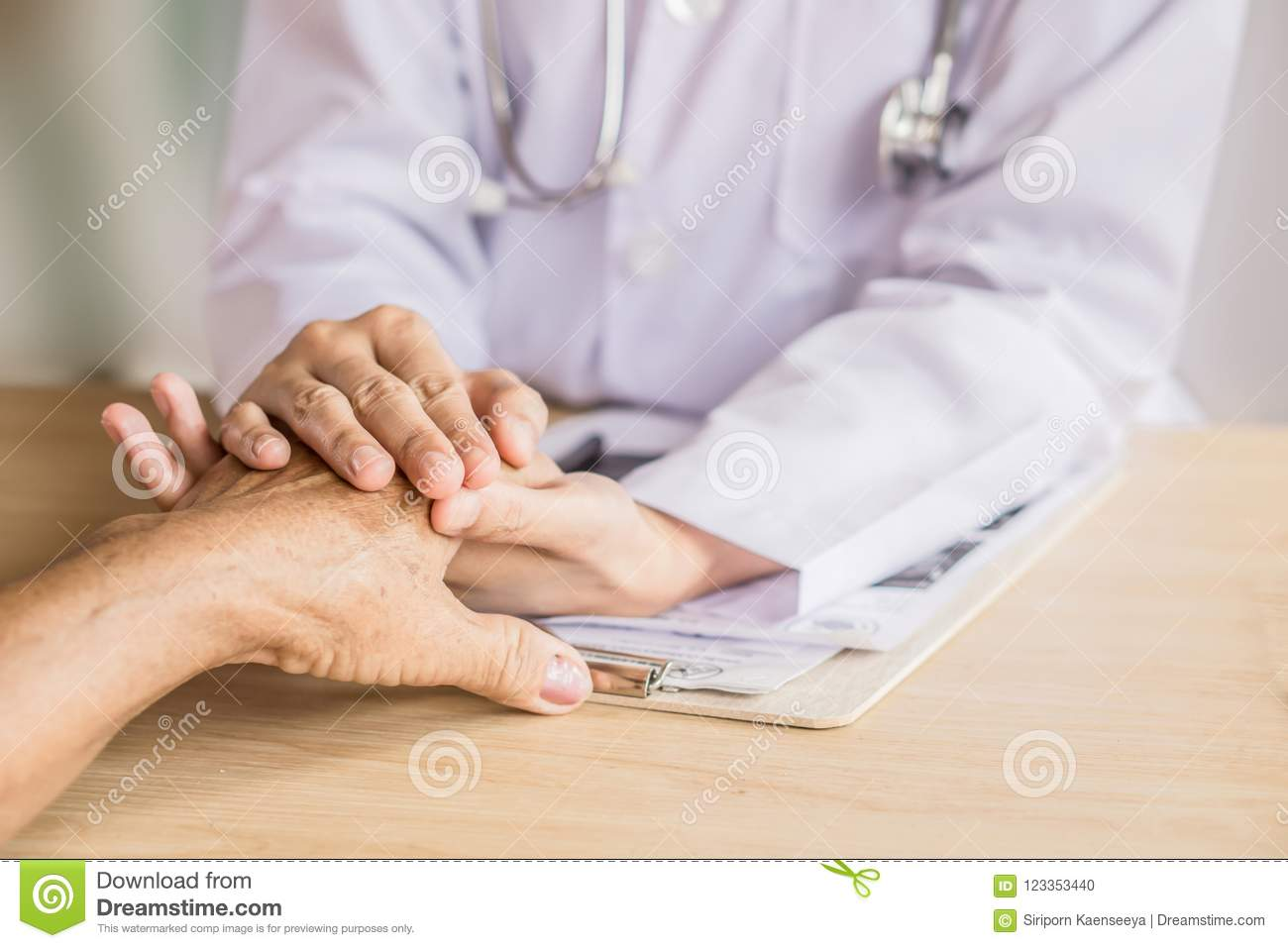 Doctor holding hand and comforting old patient in a hospital