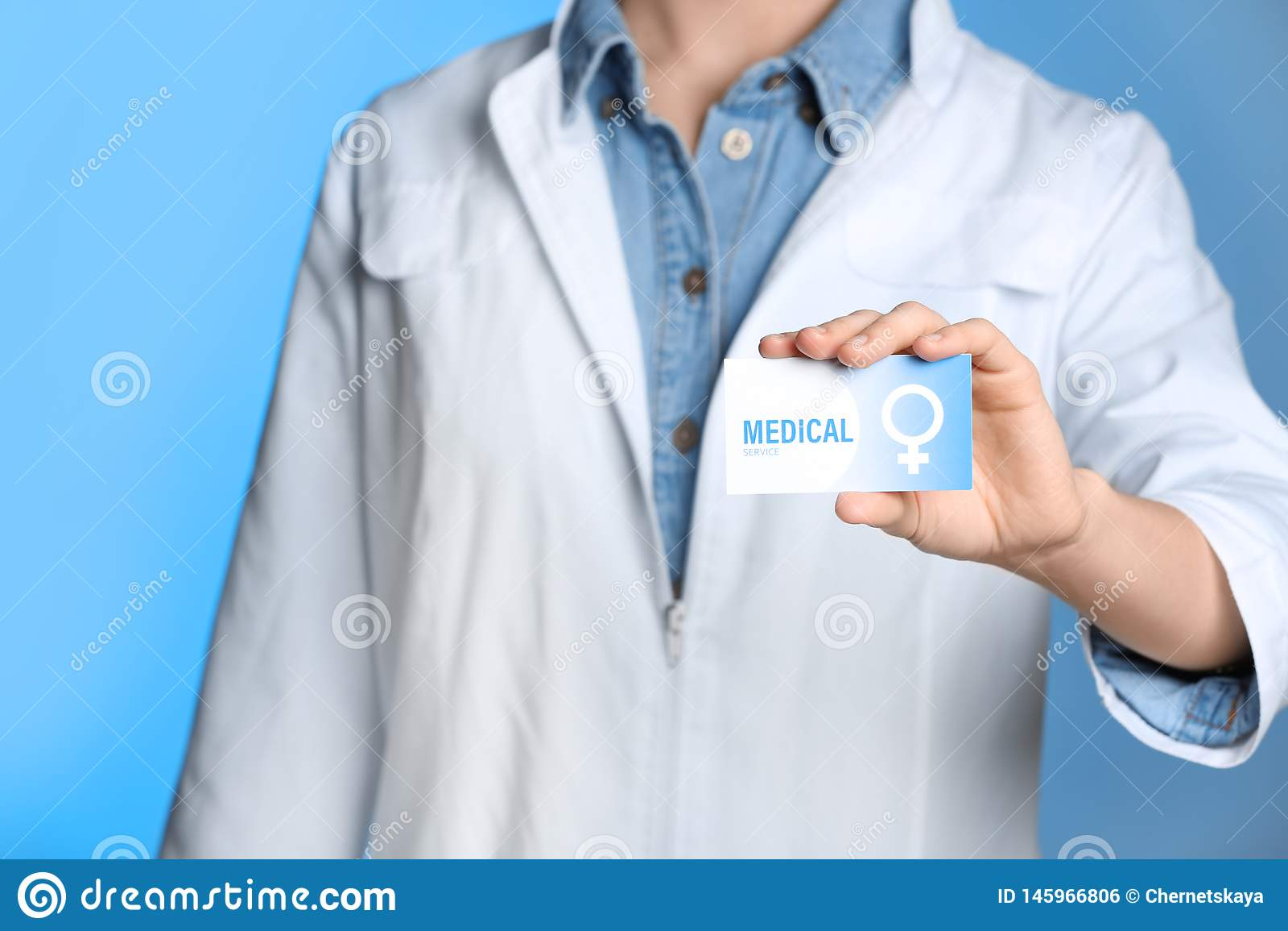 Doctor Holding Medical Business Card On Color Background