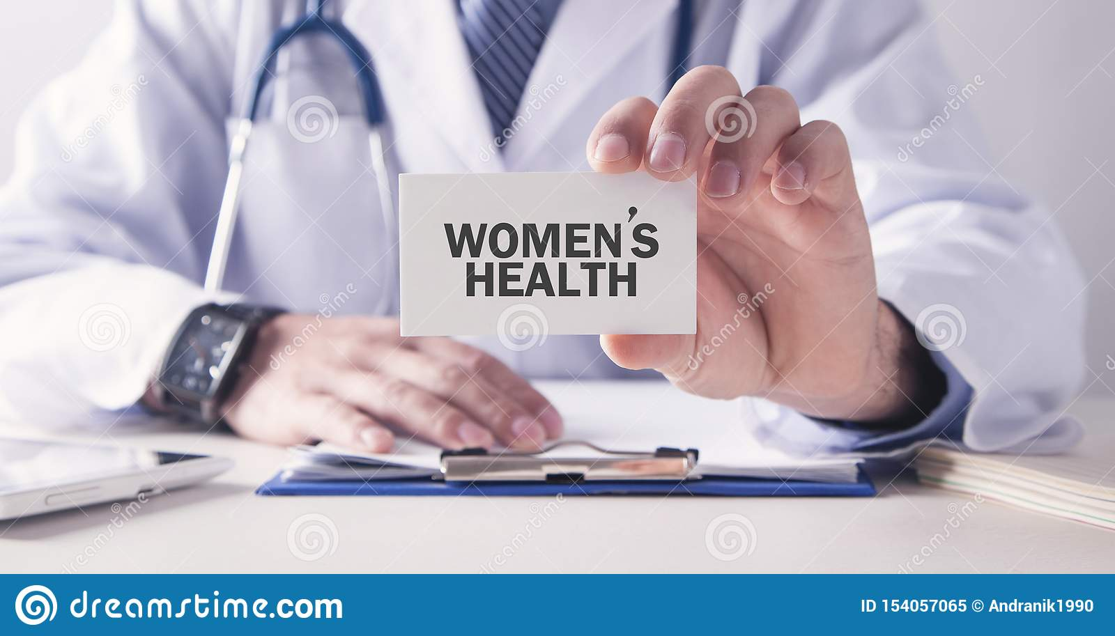Doctor holding Women`s Health text on card. Medical concept