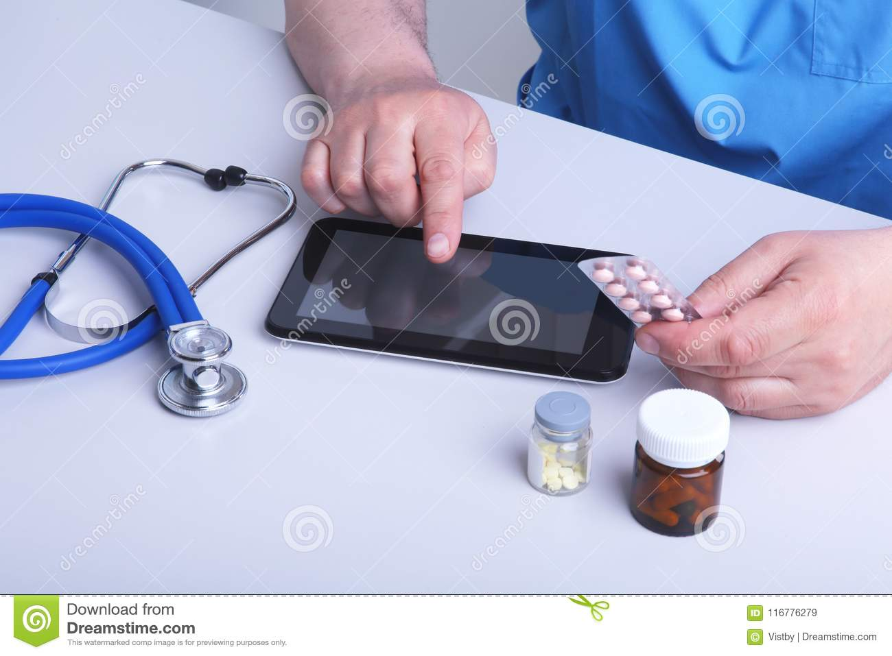 The doctor holds a blister with pills in his hand and writes out the prescription in the workplace close-up. prescribe