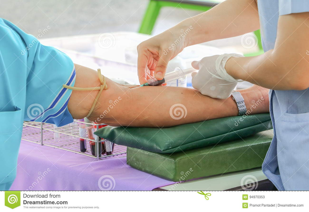 Doctor injection needle syringe on arm to collect blood for test the health