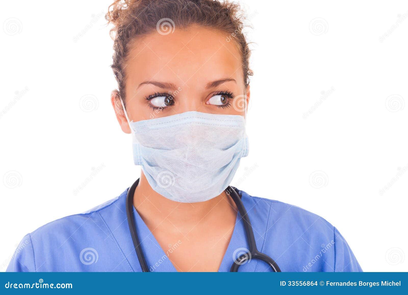 Doctor joven con la máscara y el estetoscopio aislados en el backgro blanco
