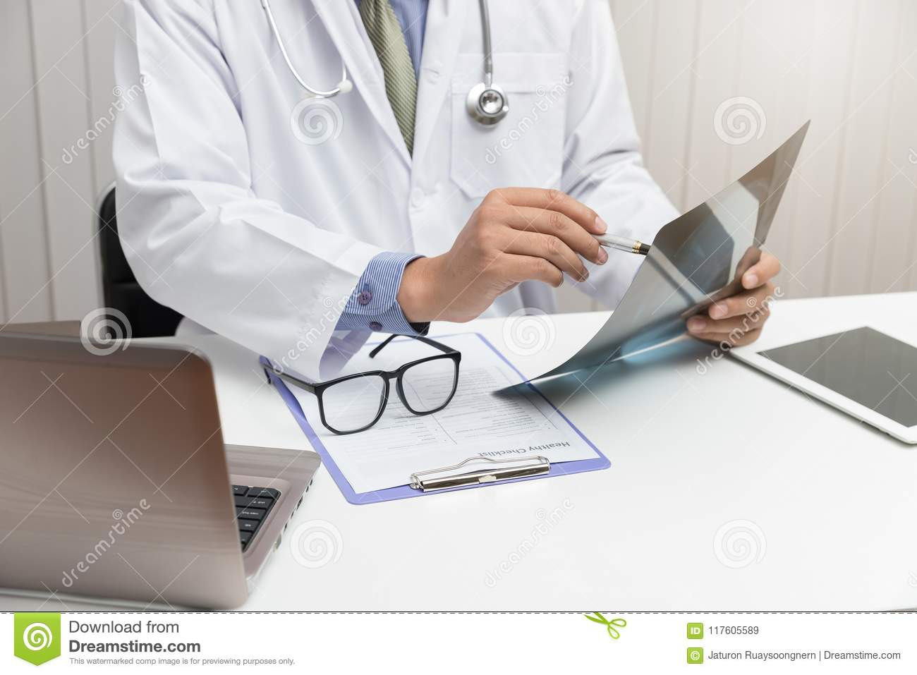 Doctor looking head x-ray film in office