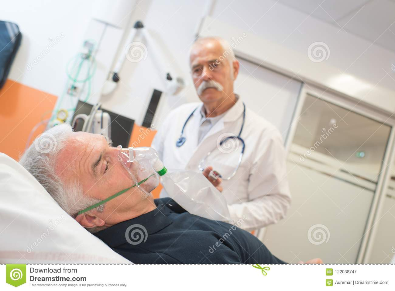 Doctor looking at senior male patient inhaling through oxygen mask