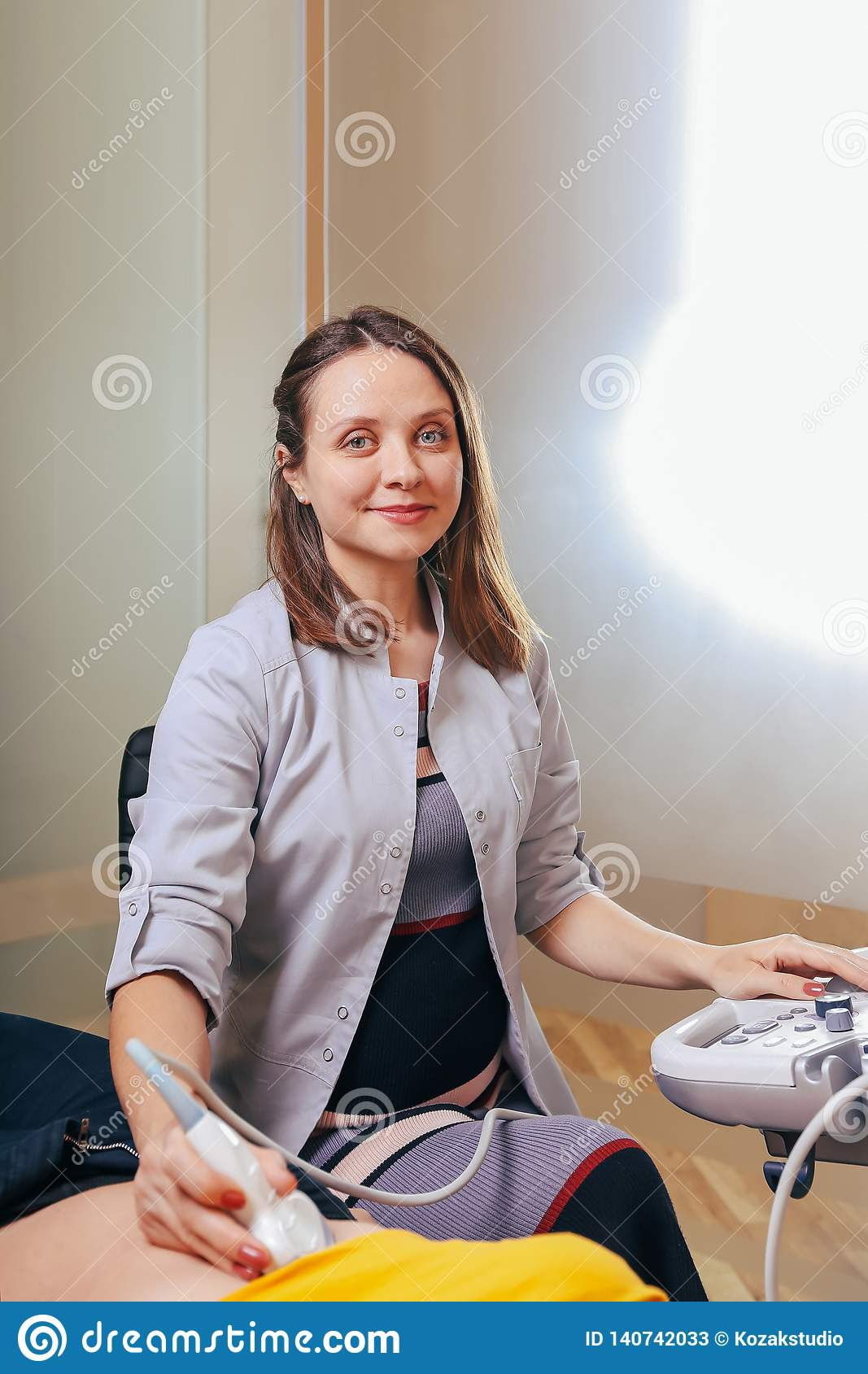 Doctor makes the patient women abdominal ultrasound. Ultrasound Scanner in the hands of a doctor.