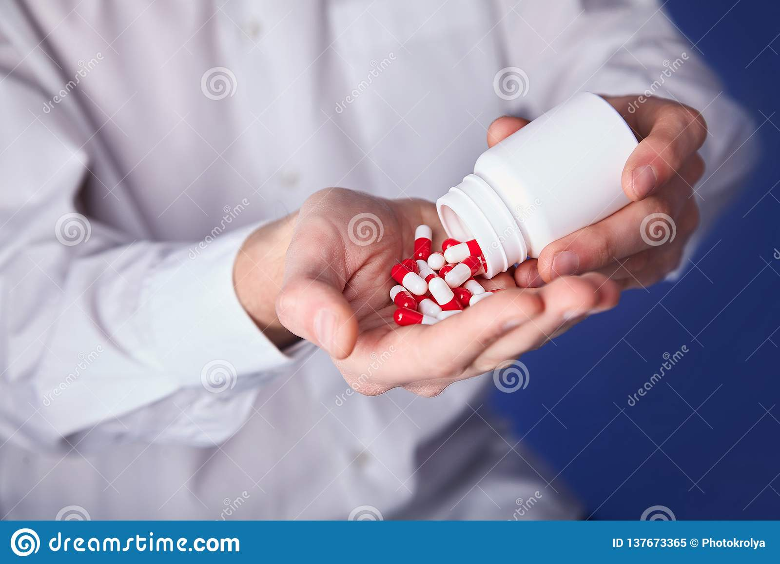Man holds multi-colored pills in hands. Panacea, life save service, prescribe medicament, legal drug store, disease healing