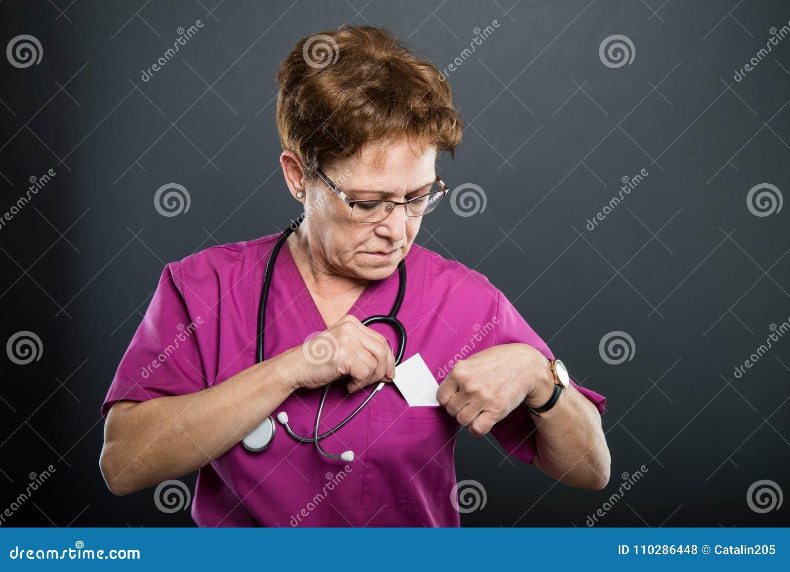 Doctor mayor de la señora que habla poniendo hacia fuera la tarjeta de visita