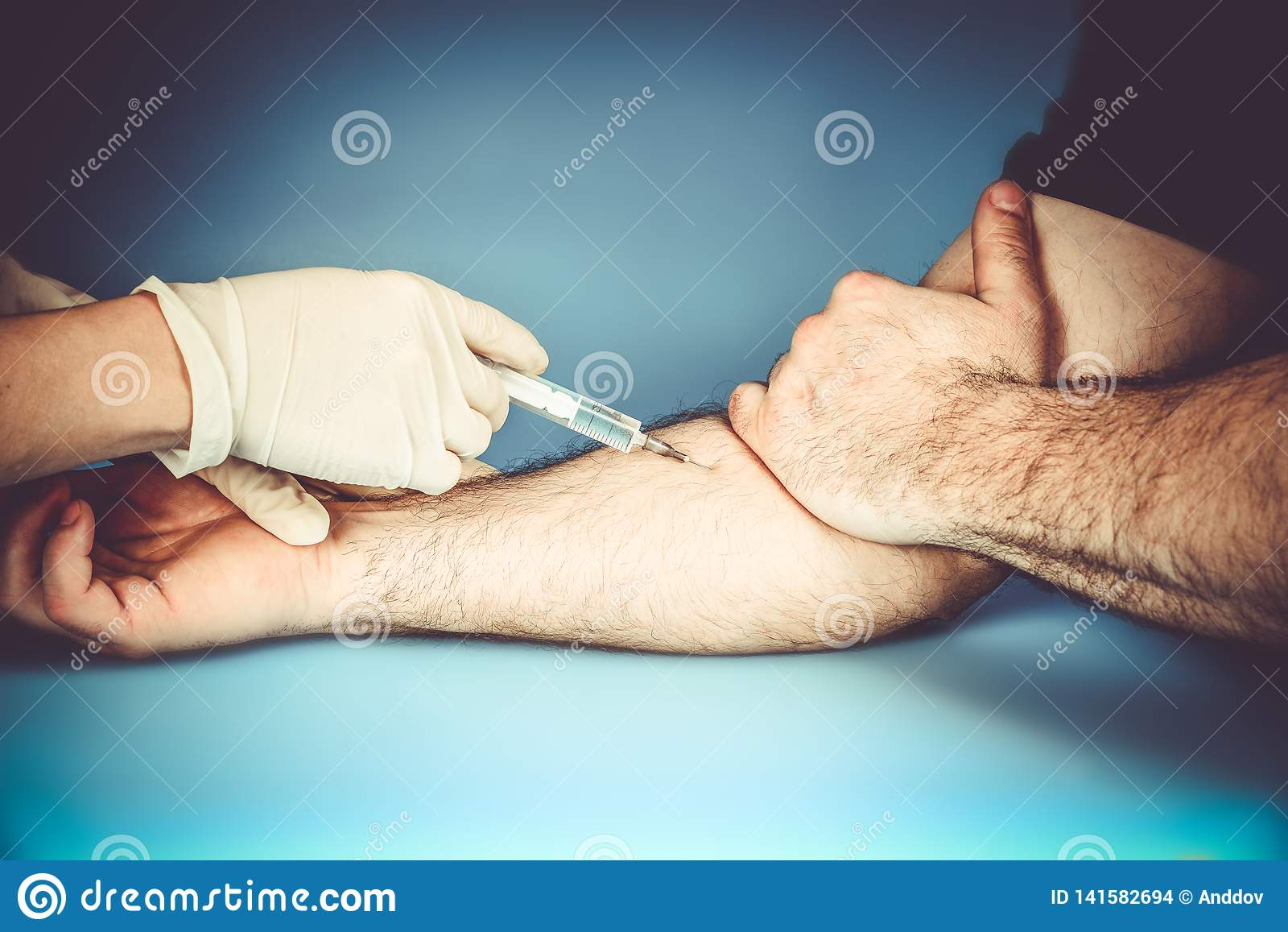 The doctor in medical gloves makes an injection intravenously to the patient during treatment to prevent the disease