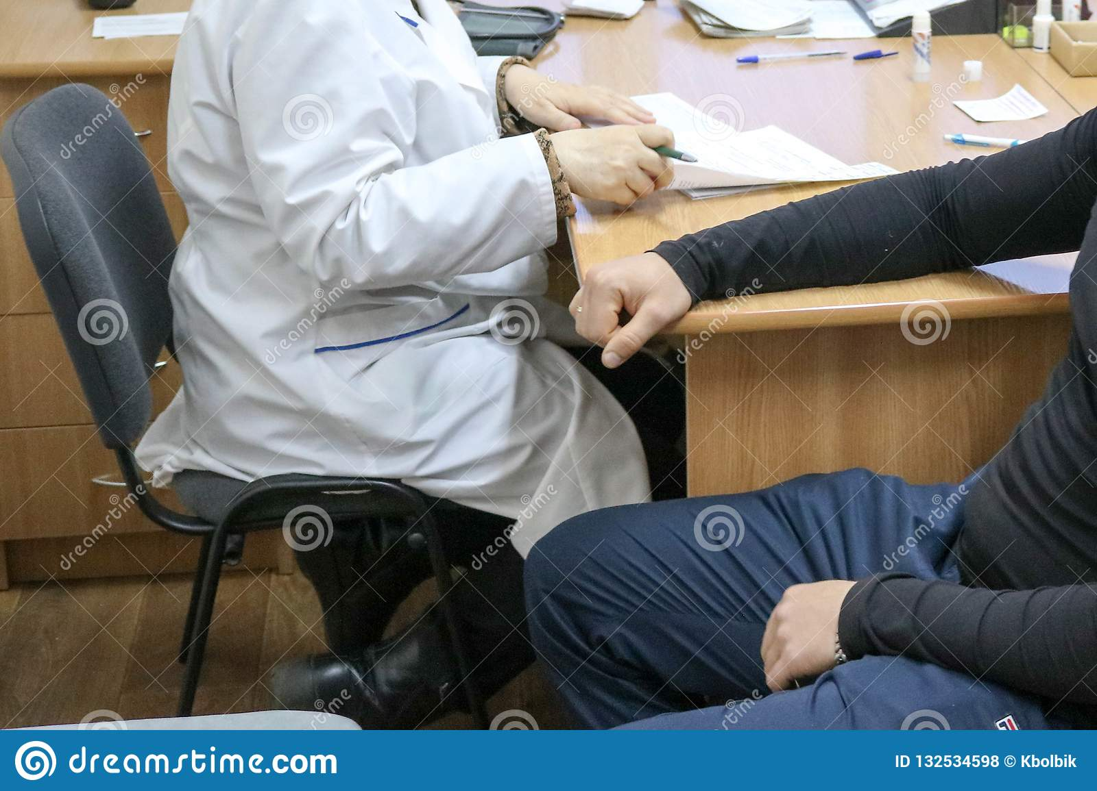 Doctor, medical worker in a white coat advises the patient of a sick man sitting on a chair in a medical institution