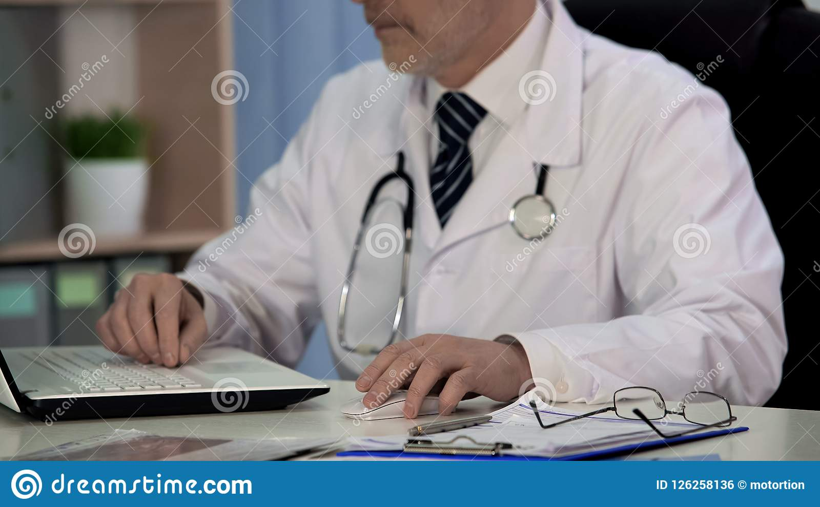 Doctor of medicine writing scientific article for magazine, working on laptop
