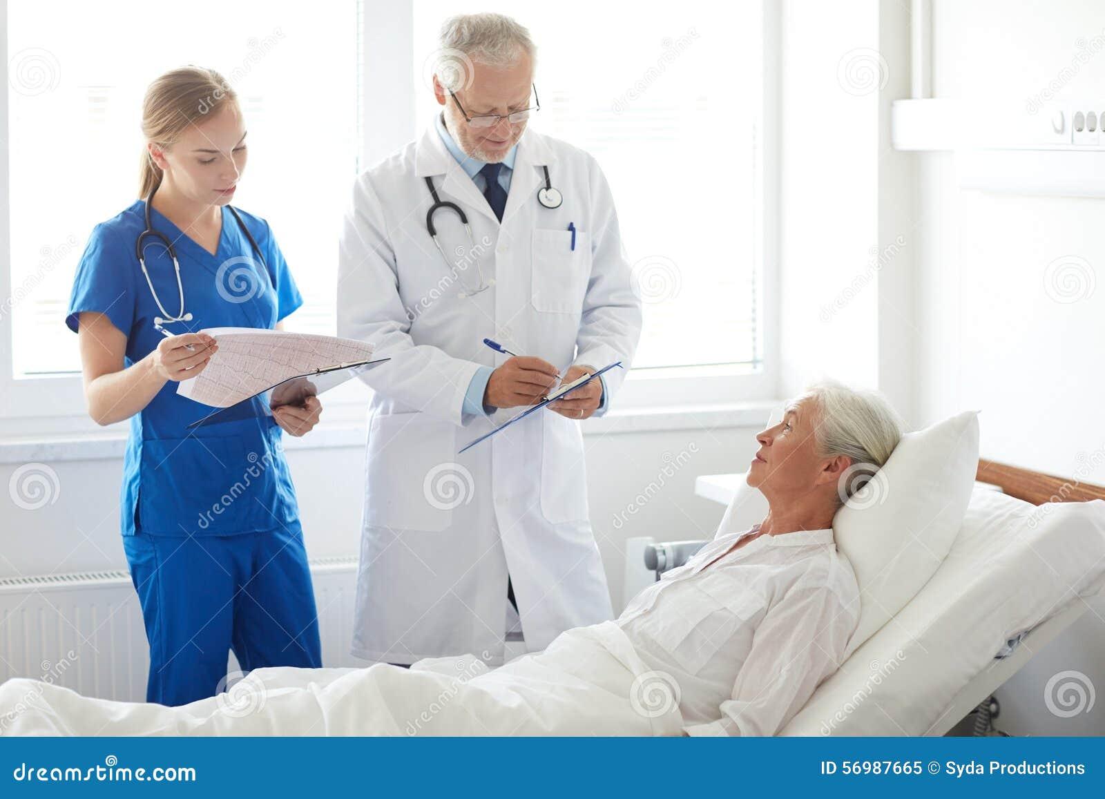 Doctor And Nurse Visiting Senior Woman At Hospital Stock Photo ...