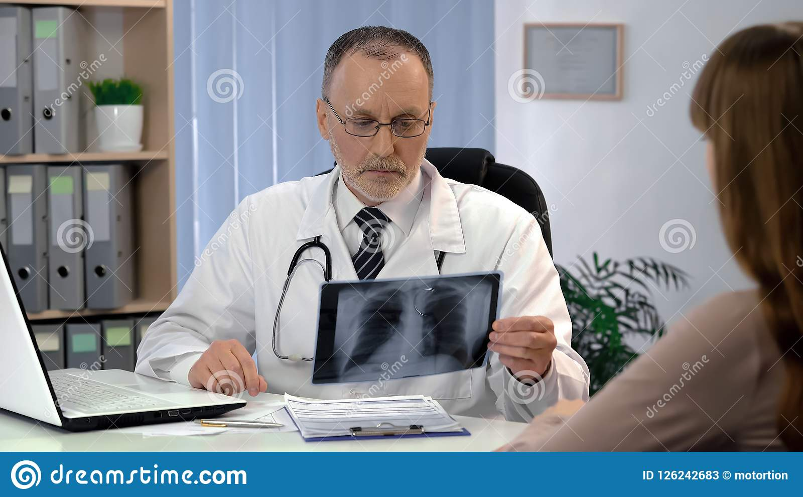 Doctor observing lungs x-ray, patient waiting for diagnosis, tuberculosis risk