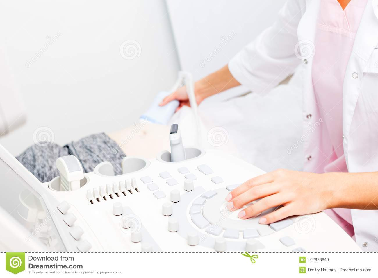 Doctor operating ultrasound machine performing obstetric ultrasonography